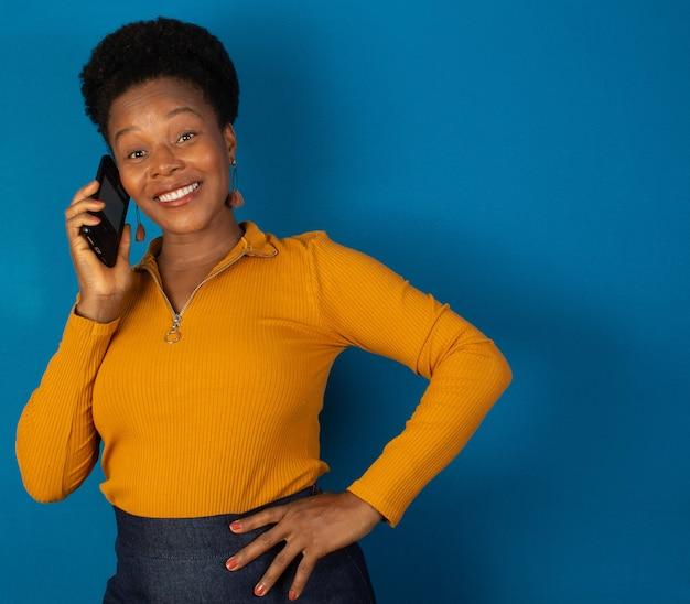 파란색 벽에 그녀의 손에 핸드폰을 들고 웃 고 흑인 여성