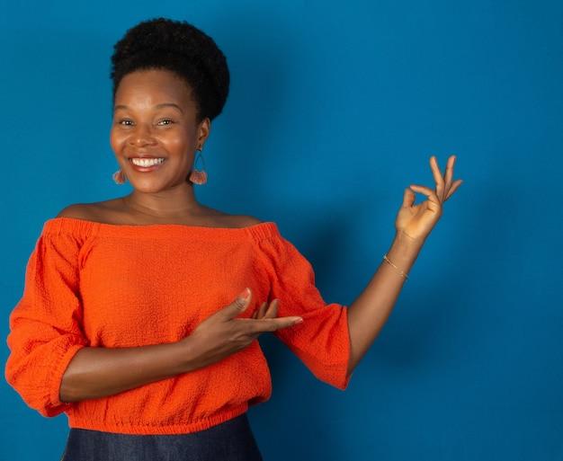 파란색 벽으로 웃는 흑인 여성