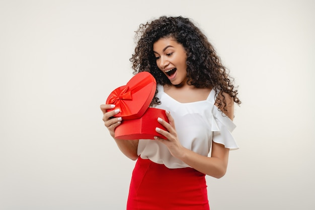 Black woman smiling with red heart shaped valentine gift box isolated