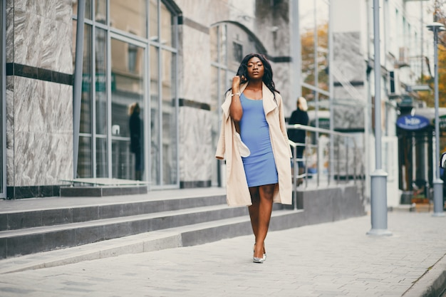 Black woman standing in a autumn city