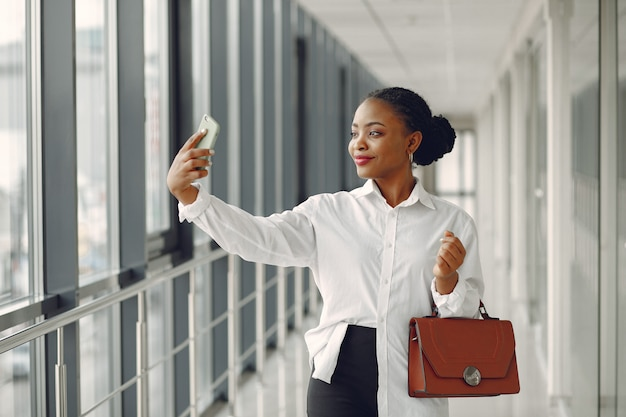 Black woman standing in the office with a laptop