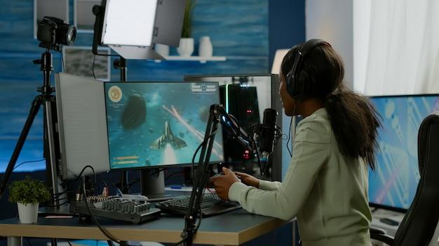 Streamer donna nera che gioca a videogiochi sparatutto spaziale con joystick che parla con i compagni di squadra in chat aperta in streaming. cyber performance su un potente computer rgb nella sala giochi utilizzando attrezzature professionali