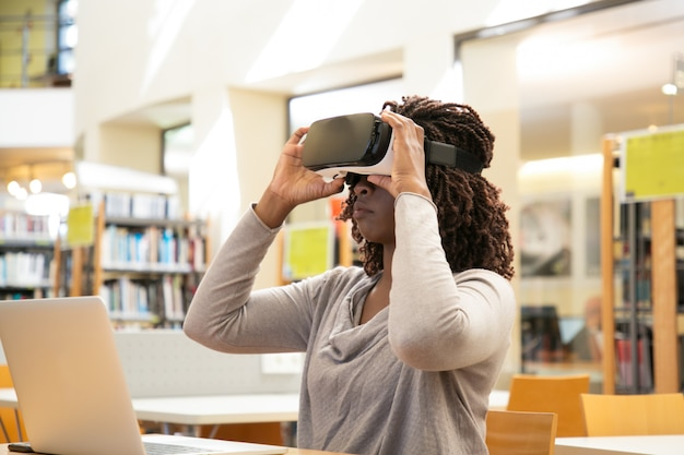 Black woman student adjusting vr headset