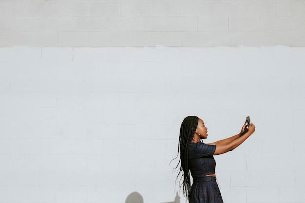 흰 벽에서 셀카를 찍는 흑인 여성