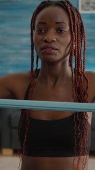 요가 스윙에 앉아 탄성 밴드를 사용하여 신체 근육을 스트레칭하는 스포츠를 연습하는 흑인 여성 트레이너...
