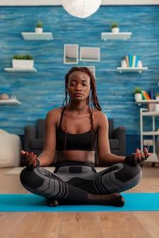 Черная женщина тренирует тело и разум, медитируя в позе лотоса с закрытыми глазами, сидя на коврике для йоги в домашней гостиной для спокойного, здорового образа жизни, одетого в спортивную одежду