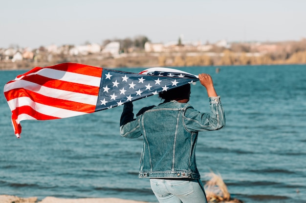 Black woman turned back holding american flag