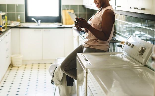 Чернокожая женщина с помощью цифрового планшета возле стиральной машины