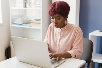 Black woman using laptop in office