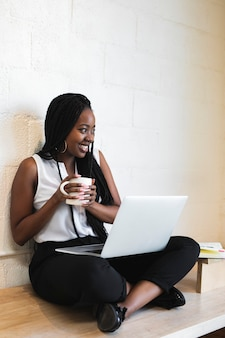 Black woman using a notebook on her laps on a wooden floor