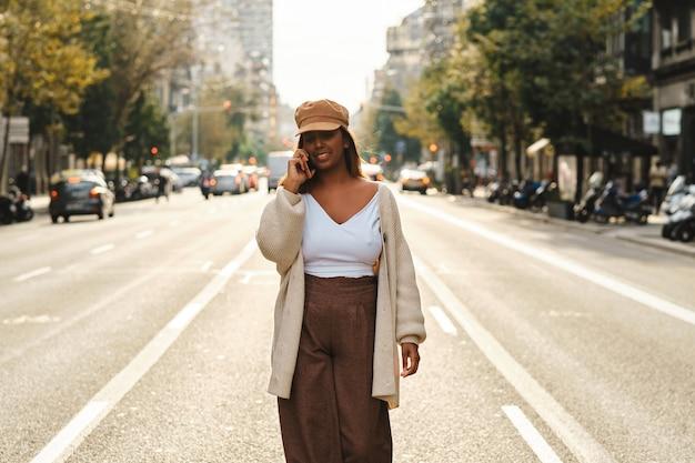 Черная женщина с помощью смартфона на открытом воздухе посреди улицы