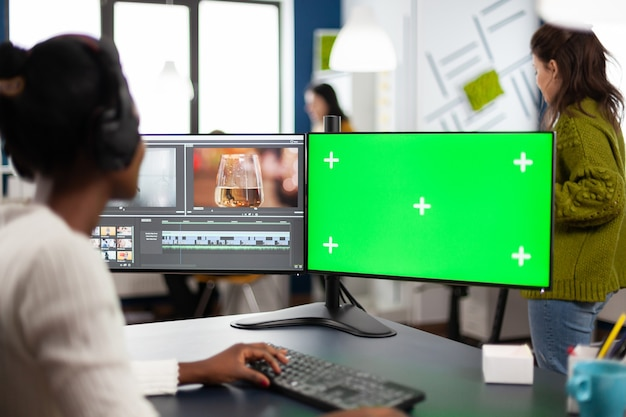 Black woman video editor developing new project film montage looking at greenscreen, chroma key isolated display of computer, sitting in creative agency