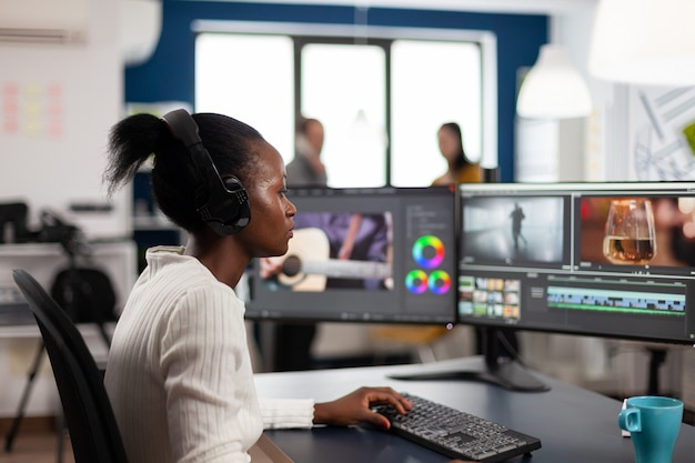 Black woman video editor developing new project film montage sitting in modern creative agency office