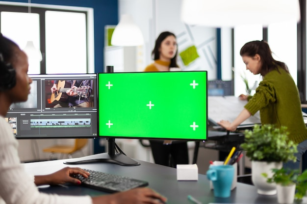 Black woman videographer employee with headphones using computer with green screen, chroma key mockup isolated display sitting in video production studio
