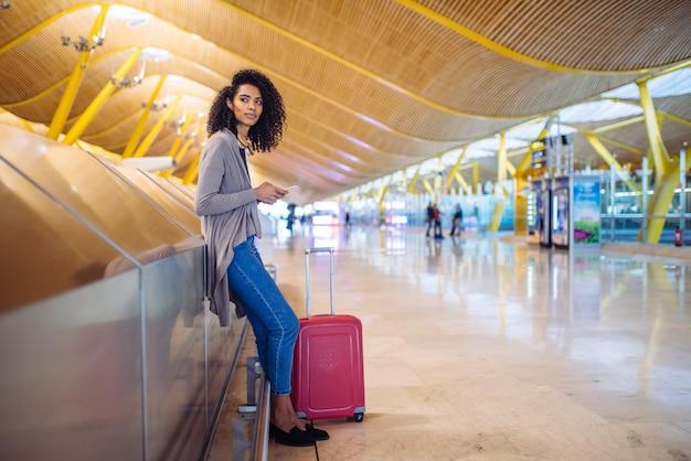 空港で携帯電話を使用して彼女の飛行を待っている黒人女性