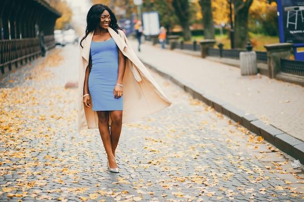Black woman walking in a autumn city
