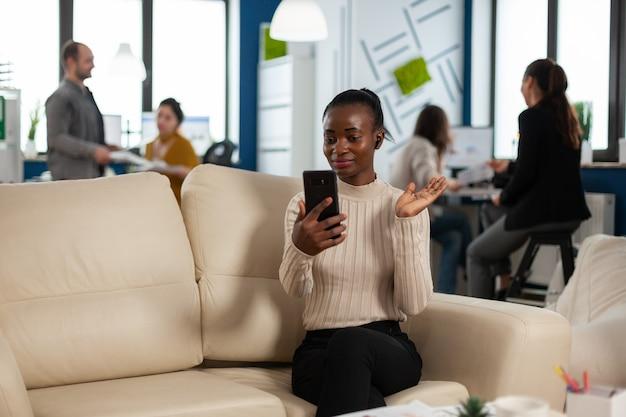 ソファに座っているヘッドフォンを使用してスマートフォンを保持しているビデオ通話でリモートマネージャーに財務報告を説明するカメラに手を振っている黒人女性