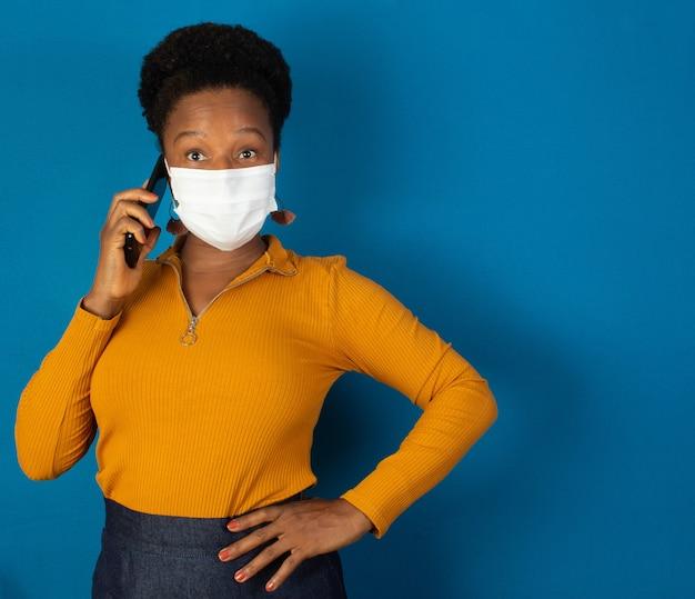 마스크를 착용하고 파란색 wallnd와 그녀의 손에 핸드폰을 들고 흑인 여성