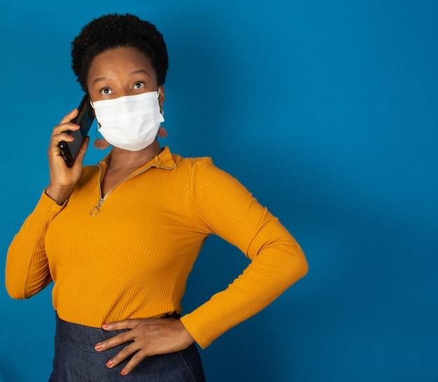 마스크를 착용하고 파란색 wallund와 그녀의 손에 핸드폰을 들고 흑인 여성
