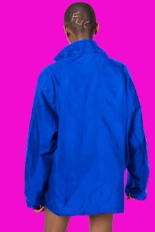 Donna nera che indossa una giacca impermeabile blu su un rosa fluorescente