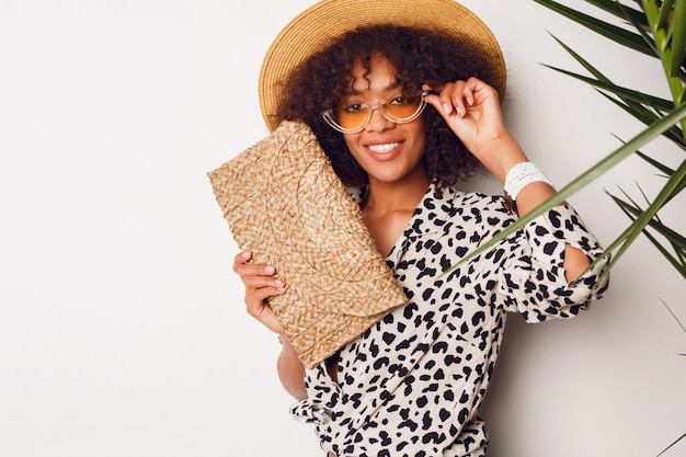 Black woman with african  hairstyle in straw hat posing over white wall. flash studio portrait.