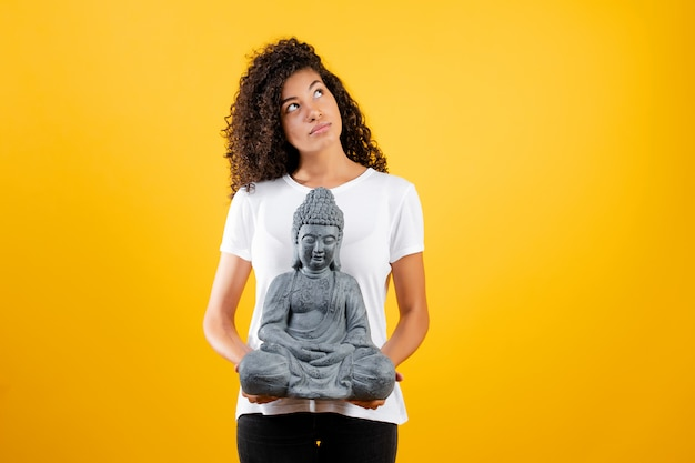 Black woman with buddha thinking isolated over yellow