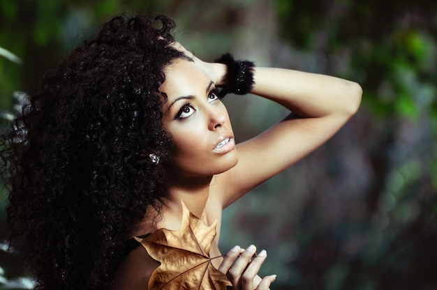 Black woman with curly hair with an autumn leaf in her hand