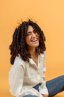 Black woman with flowers in hair laughing