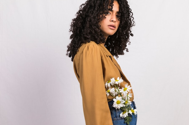 Black woman with flowers in jeans pocket