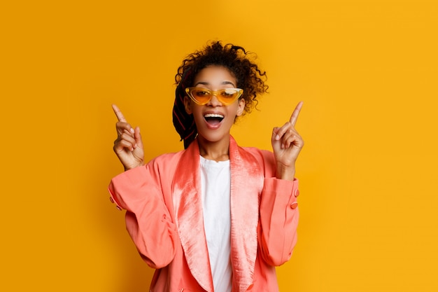Black woman with funny face pointing up. wearing casual pink jacket. yellow background .