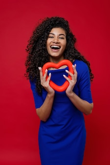 Black woman with heart shape smiling and wearing blue dress on red wall