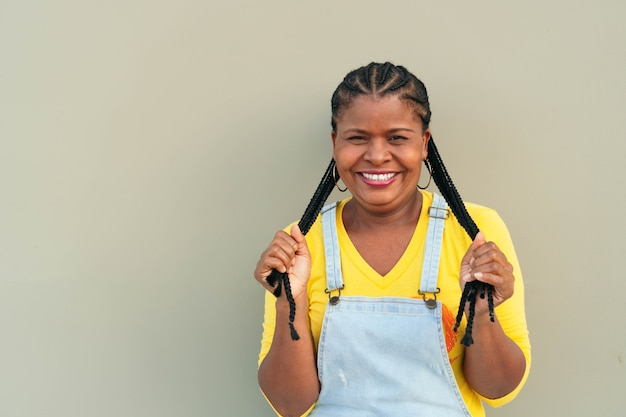 Black woman with long hair and braids standing on a gray wall - happiness