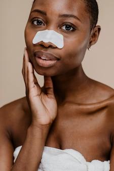 Black woman with a nose pore strip