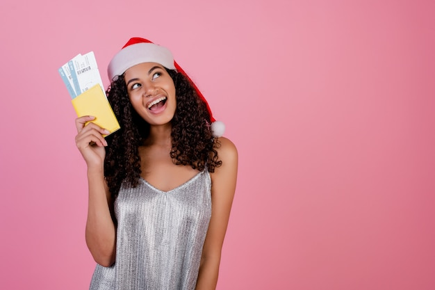 Black woman with plane tickets and passport wearing santa hat