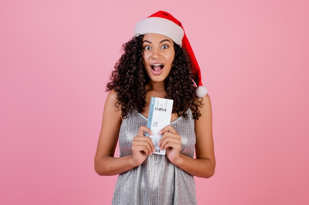 Black woman with plane tickets wearing santa hat