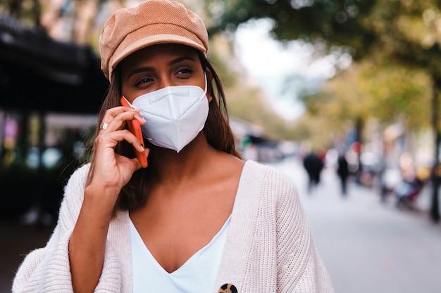 Черная женщина в защитной маске с помощью смартфона - новая норма