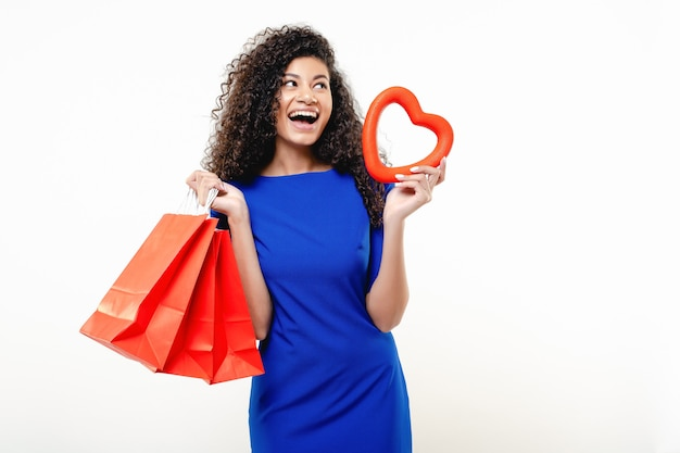 Black woman with red heart shape and shopping bags isolated