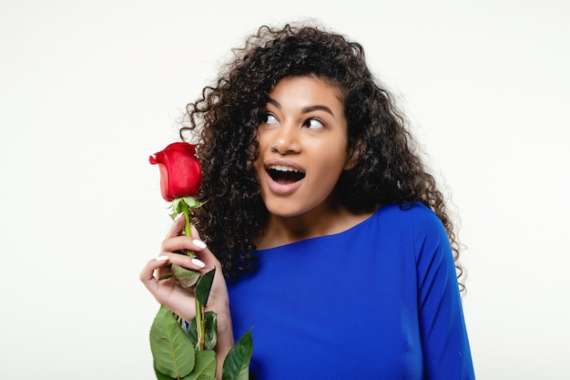 Black woman with red rose wearing blue dress isolated
