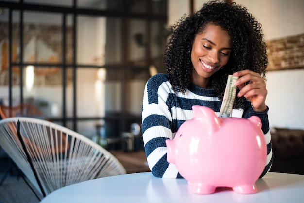 Black woman with saving piggy bank
