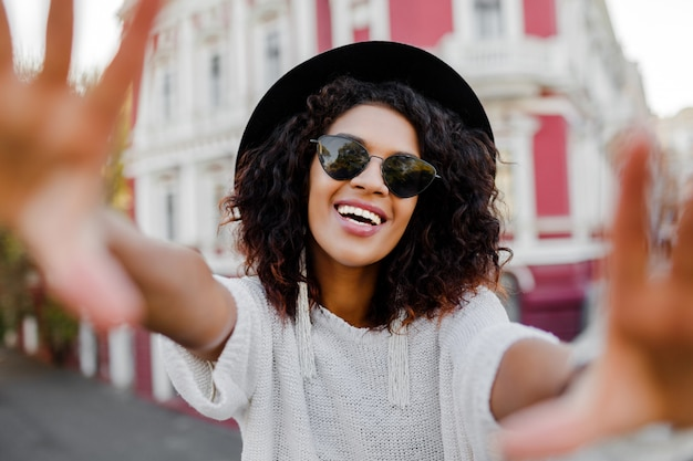 Black woman with stylish afro hairs making self portrait. wearing sunglasses, black hat and elegant earrings. happy emotions. american city background.