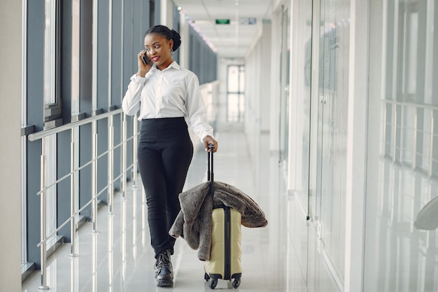 Black woman with suitcase at the airport