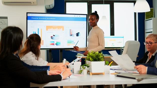 흑인 여성 노동자가 동료들 앞에서 회사 통계를 설명하고 직원 그룹을 브리핑합니다. 회의 중 전문 스타트업 금융 회사에서 일하는 다민족 기업인