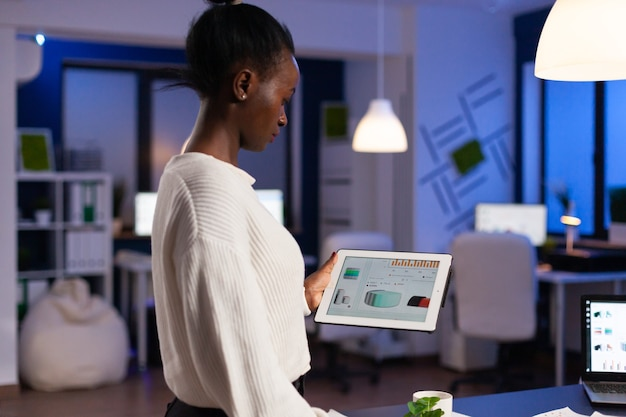 Black woman working on deadline analysing charts on tablet pc working late at night