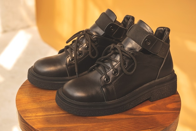 Black women boots. female autumn and winter footwear on a wooden stand. modern design photo