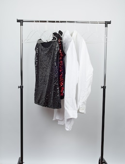 Black women's blouse with red sequins, white men's shirts hang on a white iron hanger