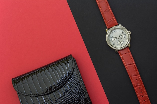 Black women's lacquered leather wallet and women's wrist watch on black and red background
