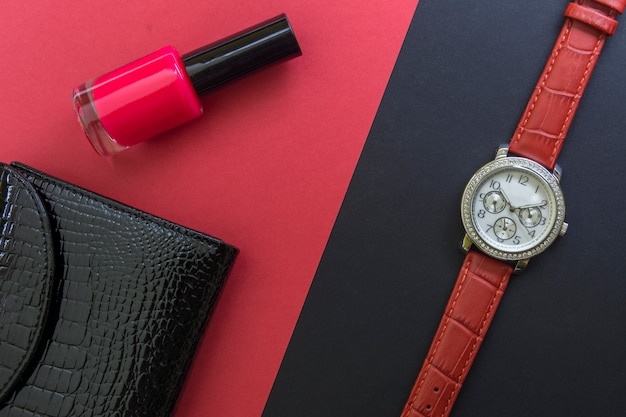 Black women's lacquered leather wallet, women's wrist watch and red nail polish red backgr