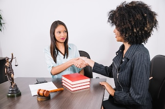 Black women shaking hands at table with books, smartphone, statue and document
