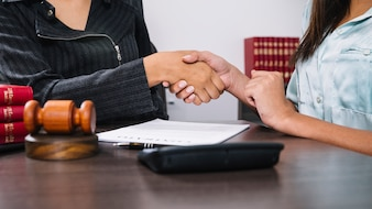 Black women shaking hands at table with document, calculator and gavel