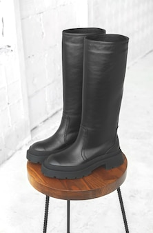 Black women wellington boots. female autumn and winter footwear on a wooden stand. modern design photo